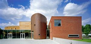 Rieten gevel bibliotheek, glazen entreehal, houten gevel grote zaal, koperen gevel trappenhuis en kantoorvleugel in baksteen
