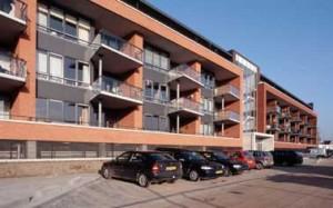 Entreezijde met kaders van baksteen, prominente entreezones en afgeschuinde balkons