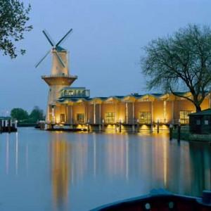 De bottel- en expeditiehal met het karakteristieke golvende dak grenst aan de Buitenhaven in Schiedam