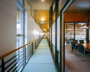 Stalen loopbrug voorzien van matglazen vloerelementen loopt als een rode draad door fabriekscomplex