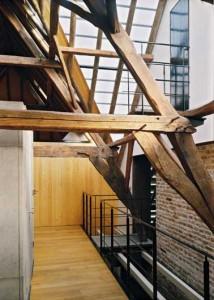 De verdieping van het voorhuis onder de glazen dakpannen met links de sanitaire cel