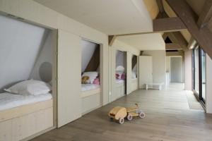 Slaapkamer met bedstedes, rechts het dakterras en linksachter vide boven keuken