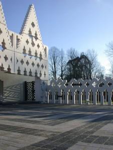 Het abstracte geometrische patroon dat de gevel siert, is verwerkt in het pleintje voor de hoofdentree. De opengewerkte gevel zet zich voort in de afscheiding van de tuin