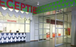 De hoofdingang is voorzien van een duidelijke receptie. Motieven in de kantwerkscreen ckomen terug in het interieur
