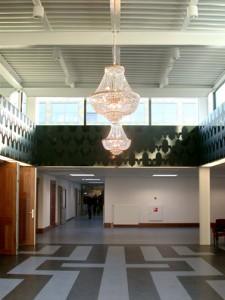 Gymzaal werd een auditorium, douche en kleedruimten werden vervangen voor een heldere foyer. In de vloerafwerking is weer een citaat van het Van der Laan-patroon zichtbaar