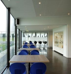 Interieur kantine met prijzenkast en doorzicht naar bestuurskamer
