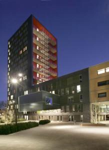 De collegezaal steekt ver uit de gevel van het binnenterrein. De verlichting aan de binnenzijde van de balkons doet de rode gevel oplichten