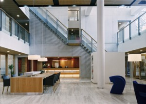 Interieur hal. De betonnen trapwand met doorloopbare gaten ensceneert ruimtelijke ervaring