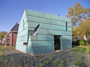 Het woonhuis valt op door zijn kleur en de dubbelgekromde gevelvlakken