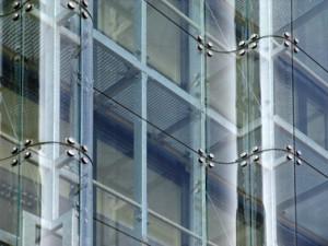 Glazenwassersbordessen en rokersbalkons achter een gordijn van hardglas, met gebogen glasplaten uit standaardmal