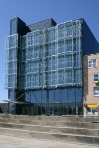 Links de geprononceerde liftschacht; de voorhanggevel begint op de tweede verdieping. Daaronder komt het grand café