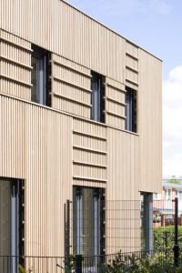 De open houten gevelstructuur geeft de woningen een lichtvoetige uitstraling
