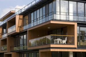 De gevels van het appartementenblok bestaan vrijwel geheel uit grote glasvlakken, waarin balkons zijn geschoven met pregnante houten kaders