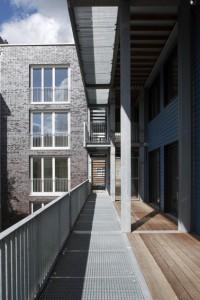 De dubbelhoge galerij geeft licht en lucht in de woningen