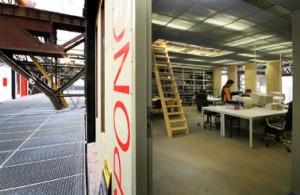 Straat op niveau 1, de oude draagconstructie doorsnijdt de persroosterplaten. Rechts een inkijk in een van de werkplaatsen, met een trap naar de derde laag