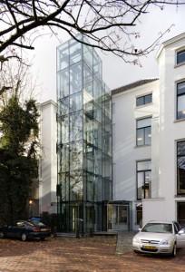 Een strakke glazen liftschacht verbindt via glazen loopbruggen op alle verdiepingen oud en nieuw
