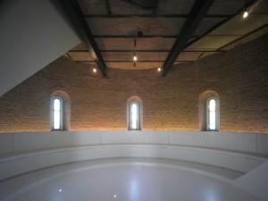 Meditatieve ruimte met trappenhuis en banken rondom, verlicht door peertjes aan het plafond, indirecte verlichting achter de banken en kleine spotjes in de vloer