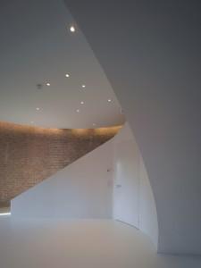 Het nieuwe glanzend witte element contrasteert sterk met de oude bakstenen muren. Deur volgt de ronding van het element