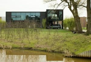 Tuinzijde met links de open gevel van de woning en rechts de kantoorvleugel