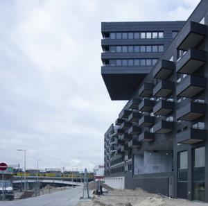 Aan het Westerdoksplein komen op maaiveldniveau commerciële ruimten, en in het midden is een entree naar de bergingen en de cour