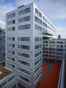 Aluminium gevelplaten en betonnen randen om brede vensters kenmerken de hofgevels van de Architekten Cie.