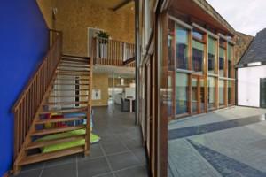 De puien aan de binnentuin met houten kozijnen, veel glas en openslaande deuren