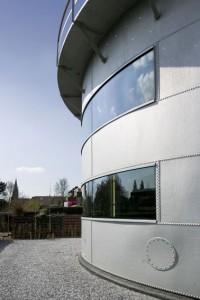 Aan de achterzijde vervangen twee glazen panelen de stalen. Rechtsonder een mansgat