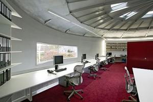 Verdieping verlicht door nieuw venster, daklichten en TL verlichting rond de gebogen boekenkasten