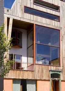 De voorgevel met dubbelhoge loggia, erker van gastenverblijf, rechts de tunctieloze ruime en boven de smalle ramen van het atelier
