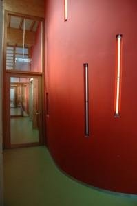 Een strooigoed van TL-buizen in de warmrode lobbige zaalwand
