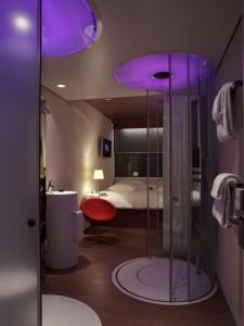 Een hotelkamer met rechts de douche, links het toilet, daarachter de wastafel en achterin het loungebed