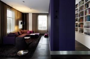 De zitkamer op de begane grond staat in open verbinding met een werkplek met een verdiepinghoge boekenkast. De tv is geïntegreerd in een apothekerskast