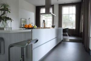 Het keukenblok staat als een lange ribbe midden in de langwerpige keuken