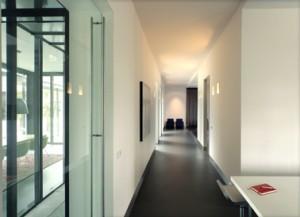Corridor aan de achterzijde verbindt keuken met aanbouw en met woonkamer. aan het einde van de corridor is de tv-hoek