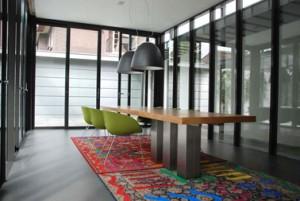 Aanbouw met tafel die vanuit een bevestiging op drie rvs kolommen de ruimte in zweeft en tapijt van Cornel en Toscani