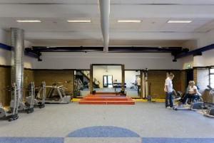 De voormalige transformatorhal is nu oefenruimte voor fysiotherapie. Twee blauwe stalen balken met transportmechaniek zijn behouden gebleven