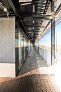 Ontsluitingsgang aan de noordzijde met natuurlijke ventilatie door middel van persroosters