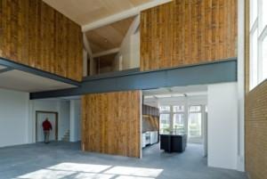De planken van de houten kerkvloer zijn hergebruikt op nieuwe wanden