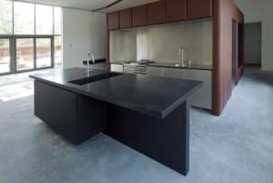 In het zwarte kunststof keukenblok zijn een werkblad, een eettafel en een van twee kanten bereikbare wasbak geïntegreerd