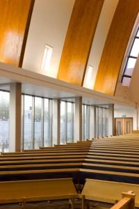Gezeefdrukt glas en stalen portalen aan de westzijde van de kerkzaal
