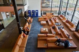 Lounge en receptie met diverse vloerafwerkingen en doorkijk naar fitnesszaal