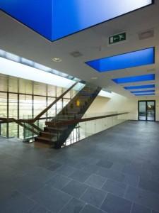 De vierkante kokers van de daklichten op de tweede verdieping zijn helderblauw geschilderd, waardoor ze bijna geen diepte lijken te hebben.