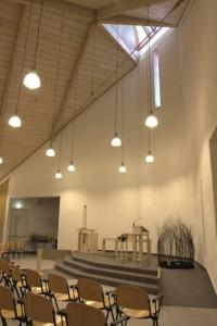 De liturgische ruimte is vormgegeven als een verhoogd stenen plateau, het plafond is bekleed met whitewashed vuren panelen