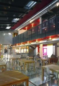 De glazen vloer in het grand café op de eerste verdieping vergroot het contact met de straat
