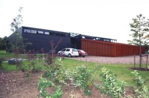 De gesloten zuidzijde, het woongedeelte steekt boven de garage uit en heeft daar ramen op het zuiden
