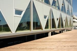 Gevelopbouw in de vorm van prefab driehoeken van gelamineerd hout met daarop aluminium kozijnen en aluminium kliklijsten