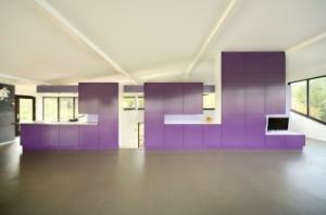 De vrijstaande, centrale meubelwand schermt de keuken en een werkhoek af en legt een verticale verbinding naar de benedenverdieping