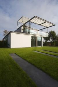 Het huis staat op een vlakke grasmat, zonder heg of schutting