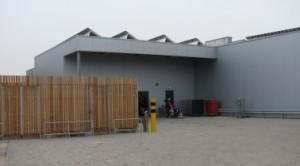 De achterzijde van het gebouw met expeditie, links de fietsenstalling en de PV cellen op het dak