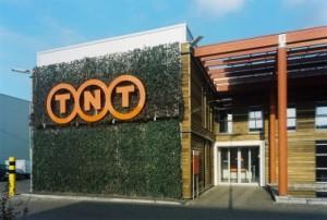 De begroeiing accentueert het logo en het groene karakter van het gebouw. Rechts de publieksingang